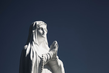 Ancient white statue of Virgin Mary against blue sky with free copy space for text.
