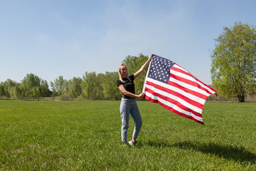 Russian girl in a black T-shirt, blue jeans and sneakers holds in her hands the flag of the United States of America waving in the wind against the background of a landscape of birches and green grass Wall mural