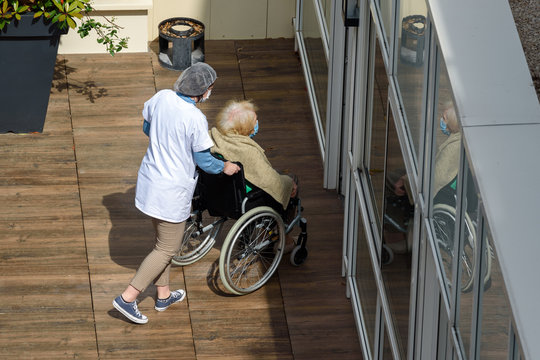 PARIS, FRANCE - MAY 13, 2020: nurse caring for an elderly and disabled woman in a nursing home on a sunny day during the coronavirus pandemic Covid-19. Both wear a protective face mask.
