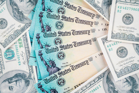Us dollar bills scattered around on table with  us treasury checks in top. To illustrate the financial help from th us government during the covid-19 crisis.