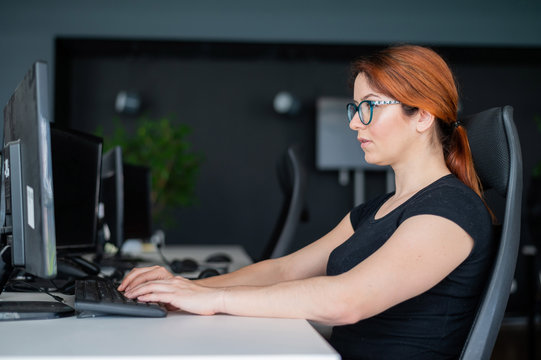 Redhead woman in glasses and casual wear working overtime. Focused girl alone works on a computer in an empty office. Deadline. The IT specialist enthusiastically works on the weekend.