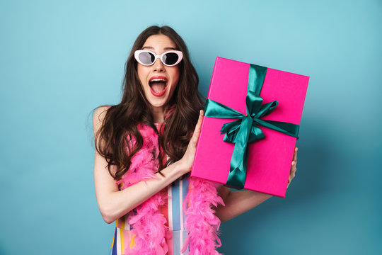 Image of surprised woman in sunglasses holding gift box