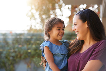 Smiling Hispanic Mother Holding Daughter Laughing In Garden At Home