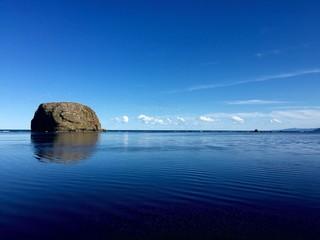 Scenic Shot Of Headland In Calm Blue Sea Fotobehang