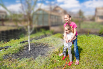 Happy and smiling siblings or sisters water the plants in the garden with hose