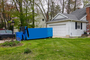 An empty blue dumpster in the driveway of a house
