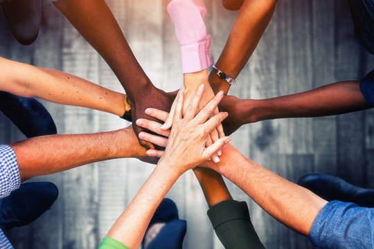 Close up view of young business people putting their hands together. Stack of hands. Unity and teamwork concept.