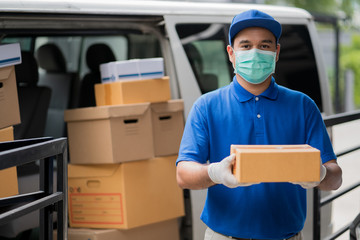 Corona Virus concept, Blue Delivery handsome asian man holding parcel cardboard box and thumbs up with protection mask and medical rubber gloves standing in front of the van