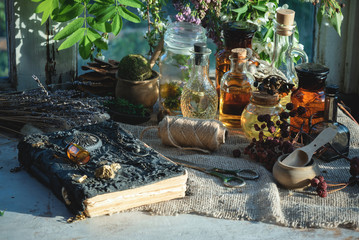 Ancient magic recipe book and magic potions in the bottle on the witch doctor table background.
