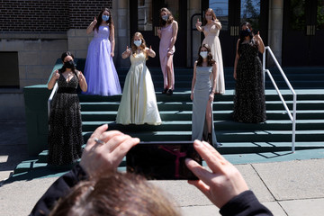 Students from Allentown Central Catholic High School in prom dresses keep a social distance as their mothers take their pictures, after their prom was cancelled during the coronavirus disease (COVID-19) outbreak, in Allentown, Pennsylvania