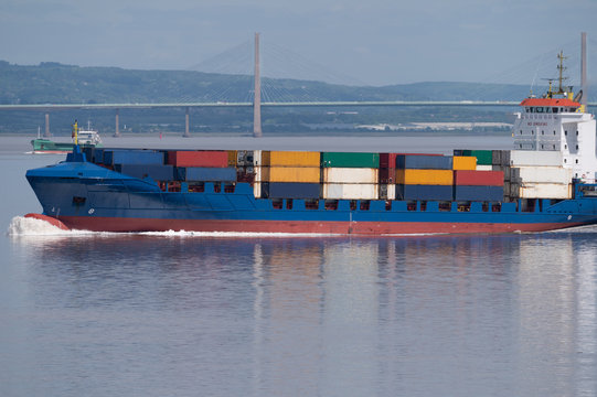A container ship passes a bridge