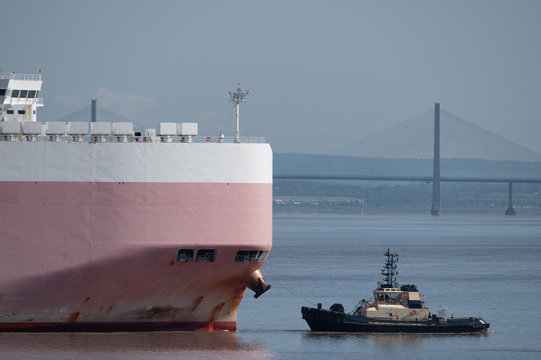 A tug leads a cargo ship