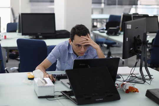 An employee of a stock brokerage firm monitors the stock prices on his computer, following the outbreak of the coronavirus disease (COVID-19), at the brokerage house in Tehran