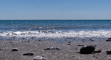 Bright sunny afternoon at the beach with shinny stones and beautiful blue ocean