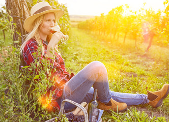 Frau trinkt Rotwein bei Picknick im Weinberg