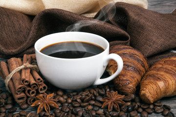 Wall Mural - cup of hot coffee and roasted coffee beans with toasted croissants