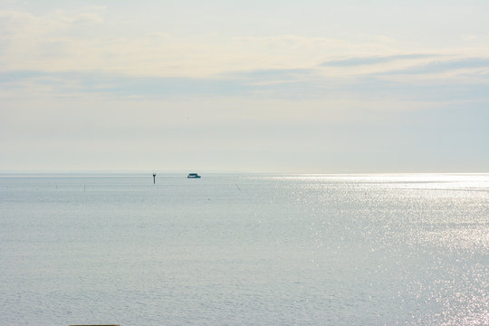 A fishing boat working crab pots on the Chesapeake Bay during a bright and sunny morning on the water.