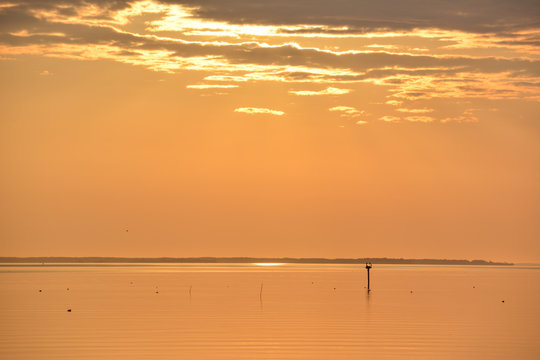 Sunrise over the Chesapeake Bay with crab pot buoys floating on the calm water surface