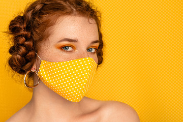 Redhead freckled woman wearing stylish handmade protective yellow polka dot cloth mask. Fashion during quarantine of coronavirus outbreak. Copy, empty space for text