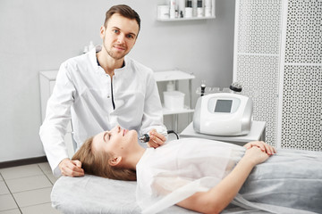 Beautician man doing anti-aging procedure of rf lifting face skin of a young woman in a white beauty parlor