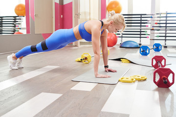 Fitness workout in the gym. Woman doing plank, exercises for abdominal muscles in colorful sportswear