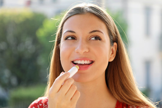 Portrait of a happy young woman applying lip balm in summer time outdoor