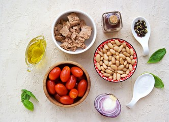 Prepared salad ingredients with canned tuna, white beans and tomato on a light concrete background. Italian food. Salad recipes.