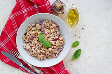 Hearty salad with boiled beans, canned tuna and purple onions in a gray plate on a light concrete background. Dressed with olive oil. Italian food.