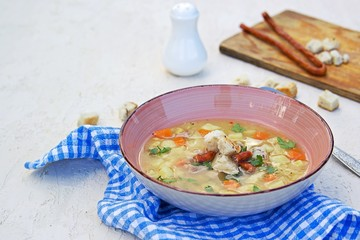 Yellow pea soup with potatoes, carrots, ham and smoked sausages in a clay bowl on a light concrete background. Served with white bread croutons.