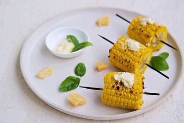 Grilled corn skewers on a white ceramic tray. Served with salted butter and grated Parmesan cheese. Vegetable dishes. Harvest the corn.