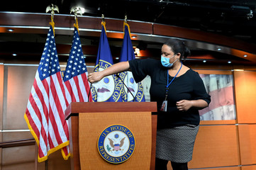 A Capitol staff person cleans the podium and microphones before House Speaker Pelosi holds her weekly news conference with Capitol Hill reporters in Washington