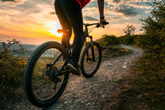 Mountain biker on trail. Back shot of mountain biker at sunset on a modern off-road bike on the hill behind the city.