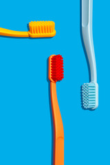 Modern Monochromatic Yellow, Orange and Blue Toothbrushes Layout on Blue Background