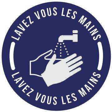 """Panneau sur les gestes barrières coronavirus """"Lavez vous les mains"""" écrit en blanc dans un rond bleu avec pictogramme de mains et de robinet"""