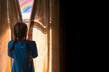 Young girl opening the curtains in a dark room to morning light and a painted rainbow