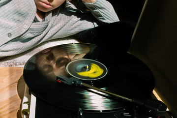 Reflection of a teenage girl on vinyl record spinning on a record player