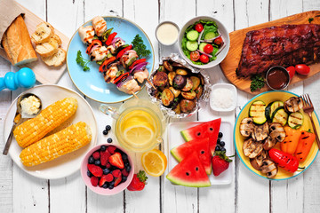 Summer BBQ or picnic food concept. Assortment of grilled meats, vegetables, fruits, salad and potatoes. Top down view table scene with a white wood background.