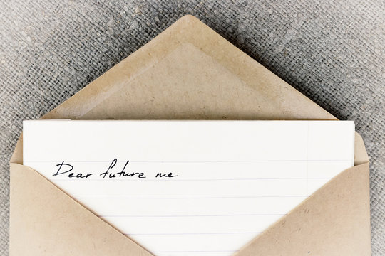 """""""dear future me"""" is written on white lined paper, which lies in an open craft envelope. The letter lies on linen cloth"""