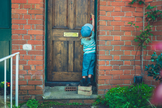 Preschooler standing on bricks to unlock front door