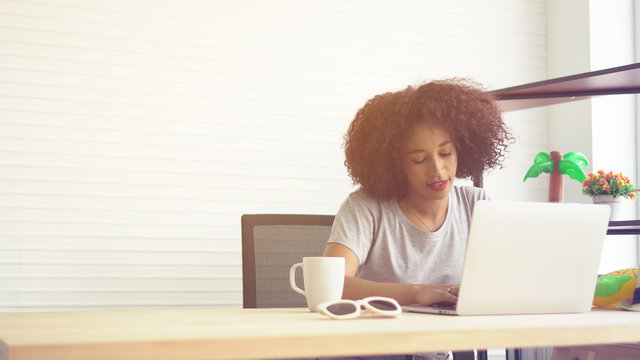African woman working from home notebook and cup of coffee
