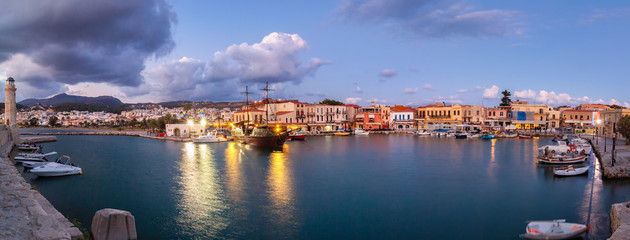 Venetian Harbour panorama with boats in front of restaurants at sunrise under colored clouds. Rethymno, Crete, Greece