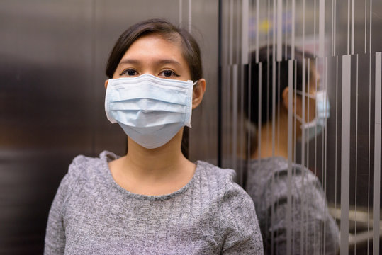 Young Asian woman with mask at corner of elevator for protection from corona virus outbreak