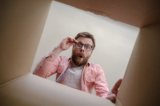 Surprised man looks into the unpacked delivered box with the order, hold glasses with hands and rejoices. Unboxing inside view.