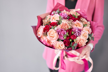 Bright berry color, Beautiful bouquet of mixed flowers in womans hands. the work of the florist at a flower shop. Delivery fresh cut flower. European floral shop.