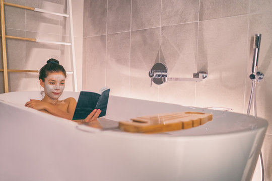 Woman taking a hot bath in modern bathtub bathroom relaxing reading a book while doing a clay face mask. Spa wellness at luxury resort hotel room.