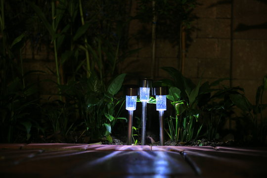 Garden LED lamp lighting. Small solar lighting shining in a garden and casting shadow in multiple direction. cool light temperature for modern hi tech landscape design.
