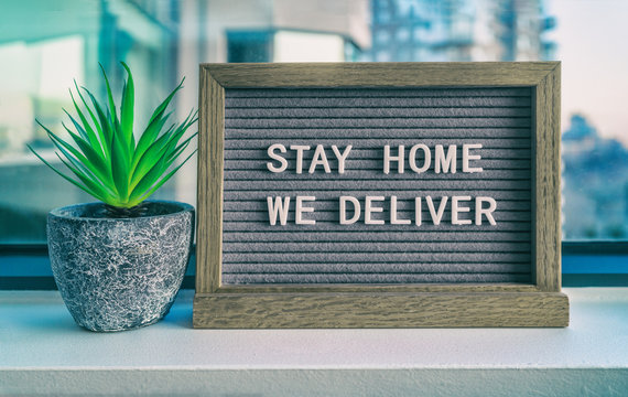 """""""STAY HOME WE DELIVER"""" Coronavirus social distancing restaurant business message sign. COVID-19 online delivery to home, staying inside. Grey felt board with plant."""