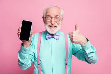 Fototapeta Portrait of amazed excited old man hold new smartphone show thumb up sign recommend suggest select wear teal turquoise shirt purple bowtie isolated over pink pastel color background obraz