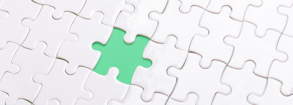 White jigsaw puzzle with with one piece missing and green background