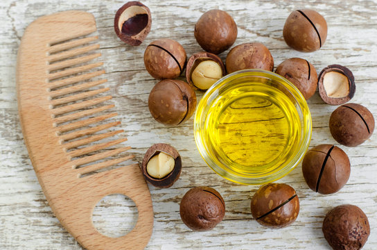 Small glass bowl with macadamia nut oil and wooden hair brush. Ingredients of homemade cosmetics - face and hair masks and moisturizers. Wooden background. Copy space.